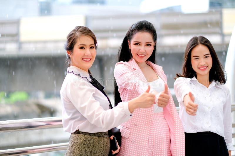 在之外的白天三个亚裔企业女孩行动与他们的工作的赞许并且微笑着表达愉快 免版税库存图片