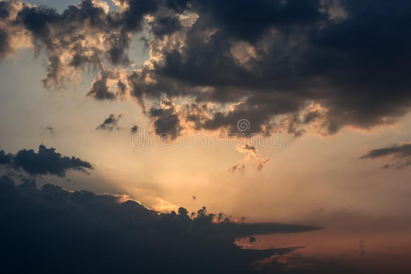 在乌云和五颜六色的天空后的太阳设置 免版税库存图片