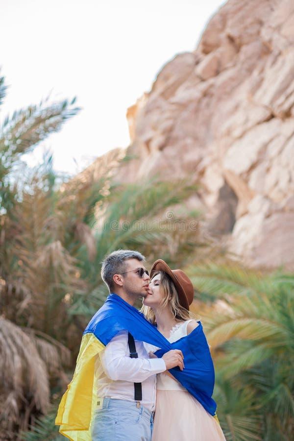 在乌克兰的旗子包裹的年轻夫妇在峡谷亲吻反对棕榈树和岩石背景  图库摄影