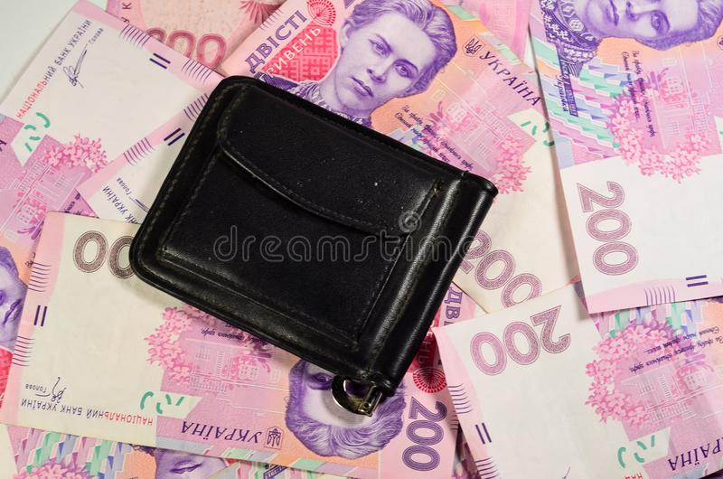 在乌克兰钞票的背景的黑金钱夹子 库存照片