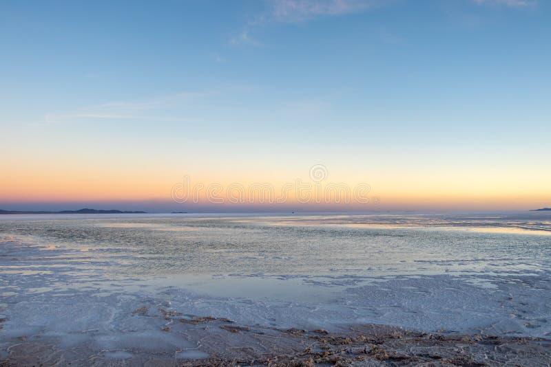 在乌尤尼盐沼盐舱内甲板在玻利维亚,难以置信的盐沙漠的日落在南美洲 免版税库存照片