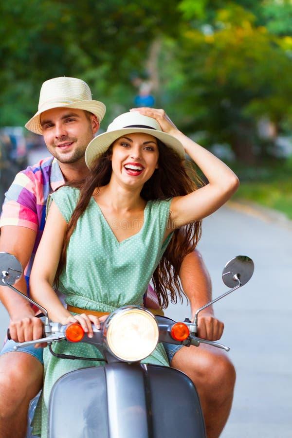 在乘坐在街道的爱的年轻愉快的夫妇一辆减速火箭的滑行车 库存图片