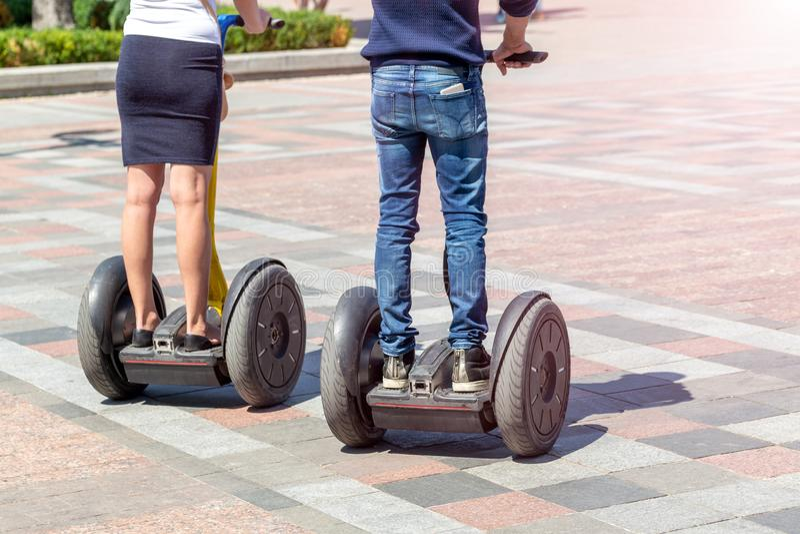 在乘坐现代电罗经滑行车翱翔的便衣的夫妇上在城市街道在明亮的晴天 电eco未来 免版税库存照片