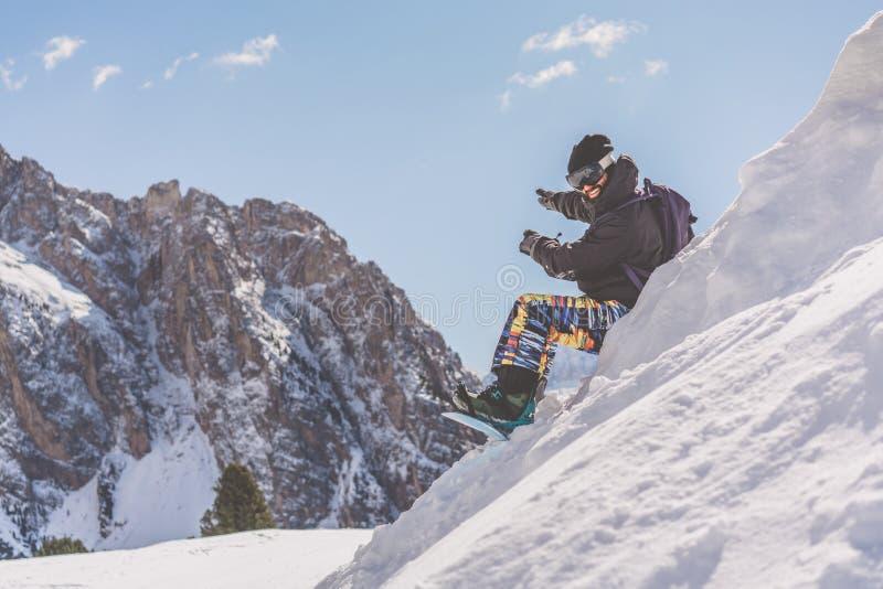 在乘驾会议以后的有胡子的微笑的snowboarded采取的休息 变冷在雪山顶部的年轻人 蠢材 图库摄影