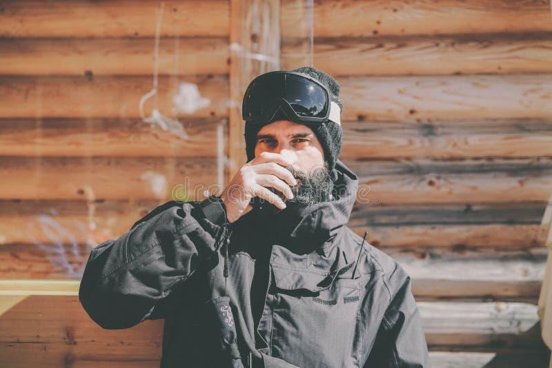 在乘驾会议以后的有胡子的英俊的snowboarded采取的休息 年轻人水杯在晴朗的大阳台的热的茶 蠢材 免版税图库摄影