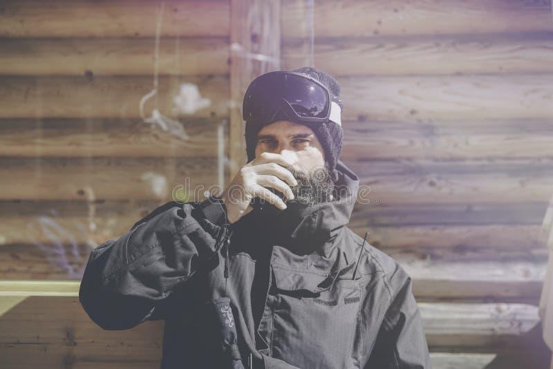 在乘驾会议以后的有胡子的英俊的snowboarded采取的休息 年轻人水杯在晴朗的大阳台的热的茶 蠢材 库存图片