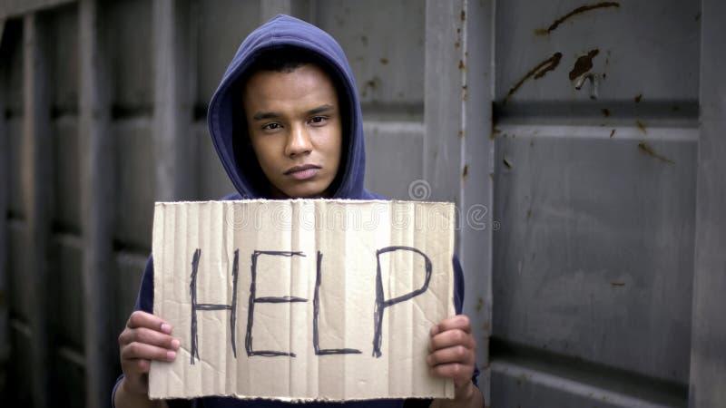 在乞求美国黑人的男孩手的帮助标志,停止战争,难民问题 库存图片