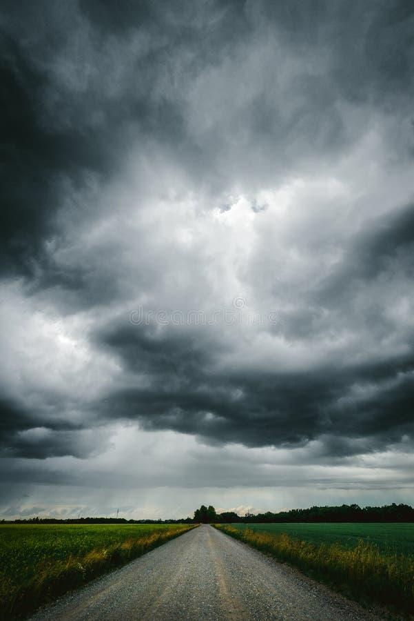 在乡下公路上的黑暗的风雨如磐的天空 免版税图库摄影