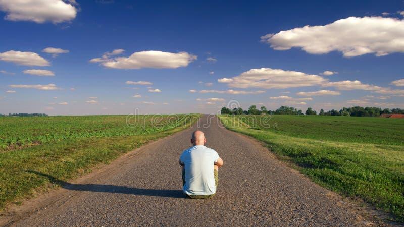在乡下公路中间供以人员坐晴朗的夏天 图库摄影