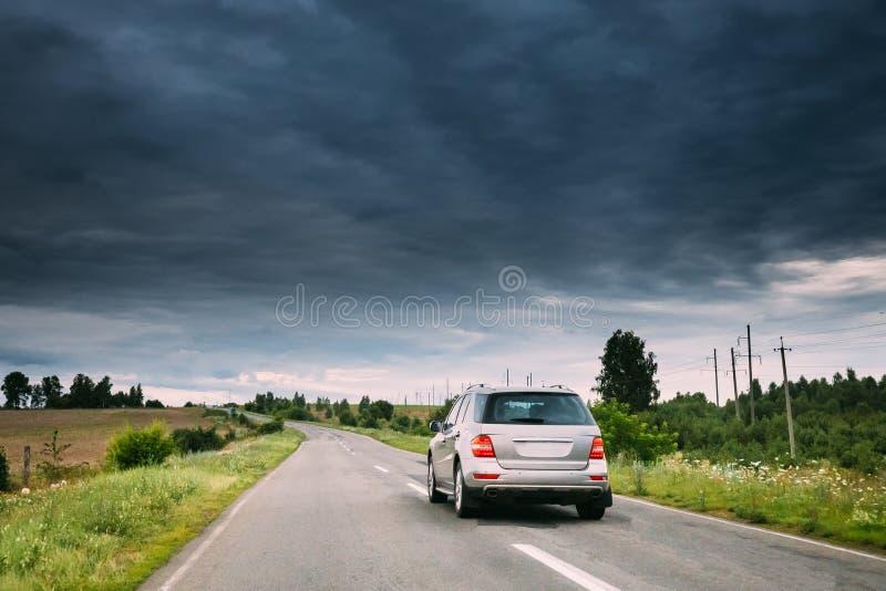 在乡下公路的灰色豪华SUV汽车在夏季 在沥青机动车路上的多云天空,高速公路 库存照片