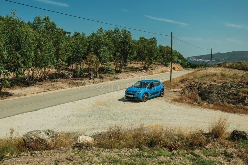 在乡下土路的汽车中止在岩石风景 库存图片