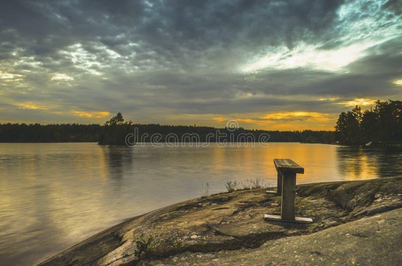 在乡下湖的被构造的蓝色云彩在一个长木凳的日落期间通过橙色天际在美好的夏日 库存图片