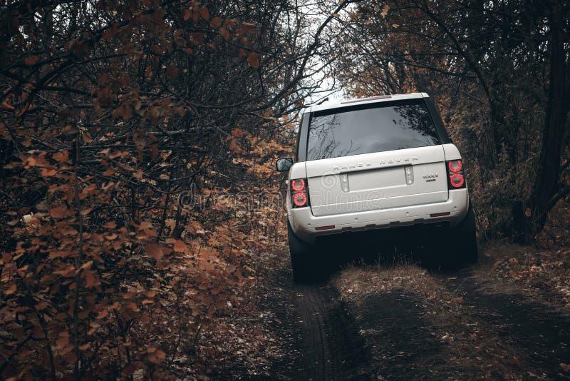 在乡下的白色汽车陆虎路华汽车立场越野在白天剧烈的云彩 库存照片