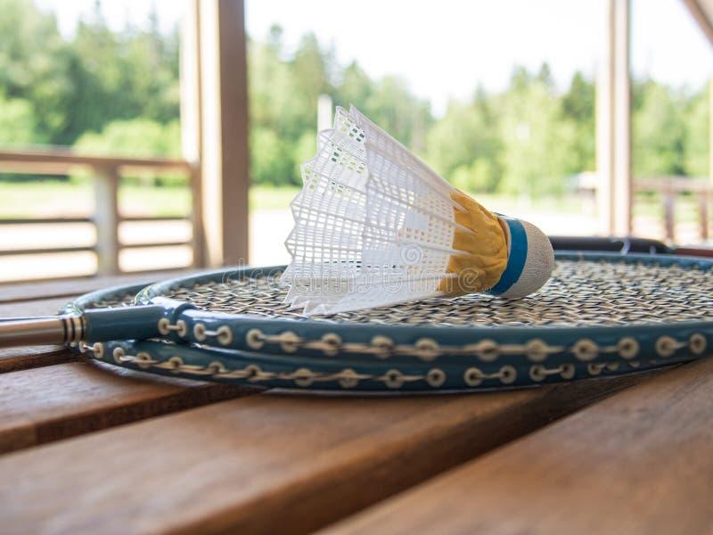 在乡间别墅的大阳台的木国家家具 两羽毛球拍和shuttlecock在一张木桌上说谎 ?? 免版税库存照片