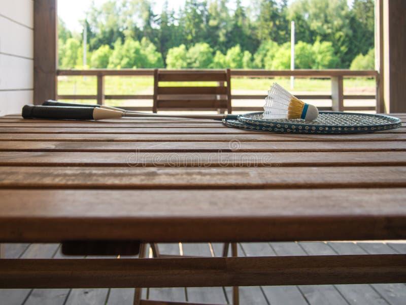 在乡间别墅的大阳台的木国家家具 两羽毛球拍和shuttlecock在的一张木桌上说谎 免版税库存图片