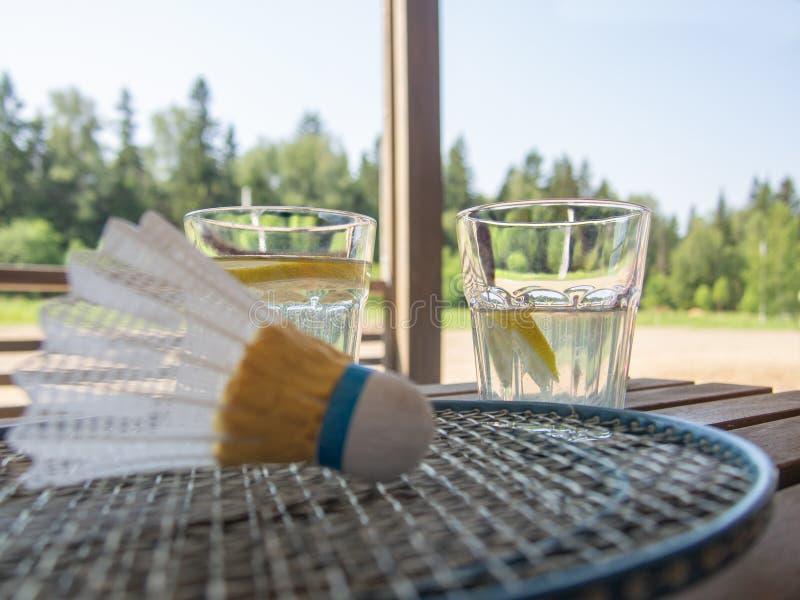 在乡间别墅的大阳台的木国家家具 羽毛球拍和shuttlecock在木桌上 与a的两块玻璃 库存图片