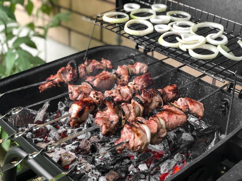 在乡间别墅附近的被打开的格栅用几乎准备好肉用里面葱 户外BBQ夏天活动 免版税库存图片
