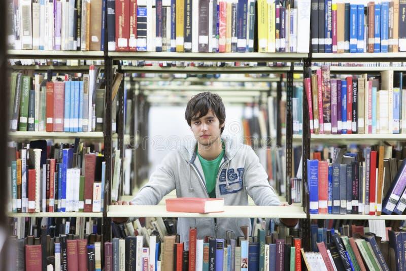 在书中的男性大学生在图书馆里 库存照片
