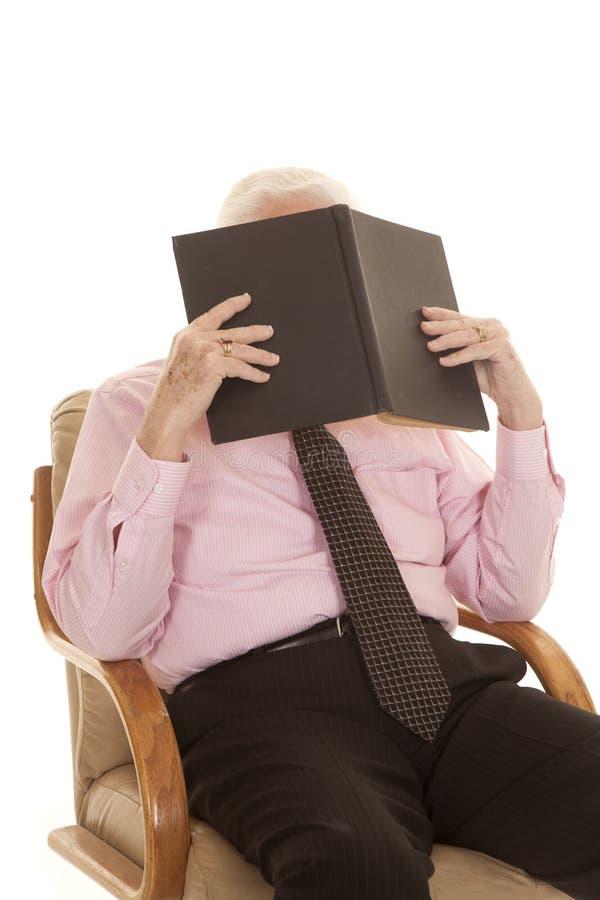 在书后的年长人桃红色衬衣 图库摄影
