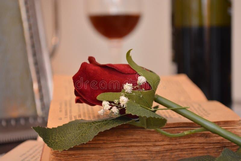 在书和玻璃红酒和瓶的红色玫瑰色花在背景中 免版税库存照片