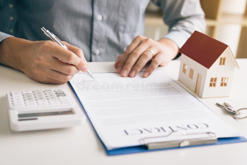在书桌上的新的购房者签署的合同在办公室屋子里 免版税库存照片