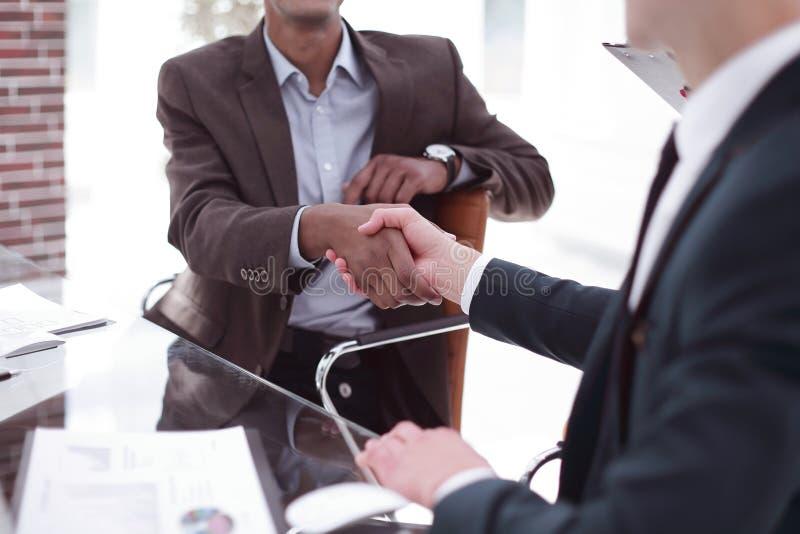 在书桌上的特写镜头握手国际伙伴 库存图片