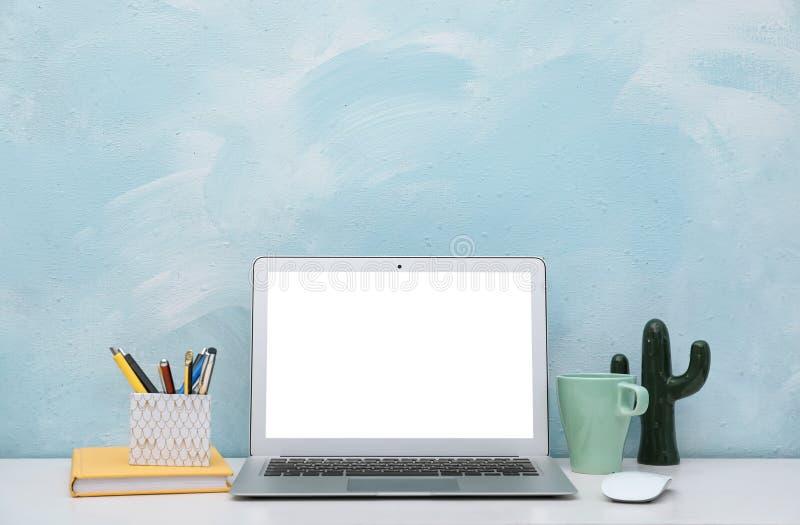 在书桌上的膝上型计算机对颜色墙壁在家庭办公室 图库摄影