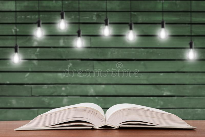在书桌上的葡萄酒开放书和在背景的电灯泡 免版税库存图片