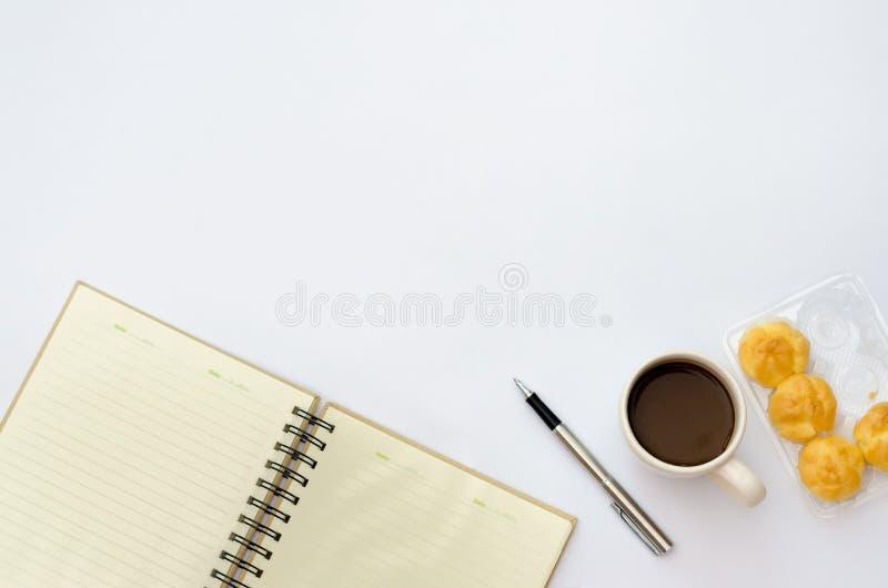 在书桌区域空间的空间输入文本 大模型咖啡杯快餐糖果,笔在一张白色台式视图书桌安置的便条纸ta 免版税库存照片