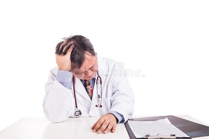 在书桌后安装的沮丧的哀伤的成熟的亚裔医生 免版税库存照片