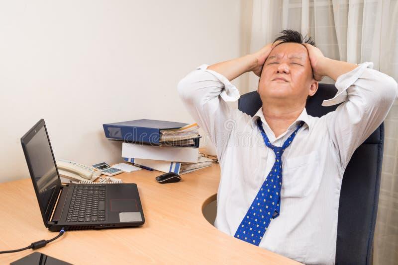 在书桌后的沮丧和紧张亚裔业务经理在o 免版税库存图片