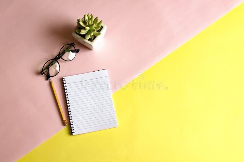 在书桌和玻璃安置的笔、笔记本 图库摄影
