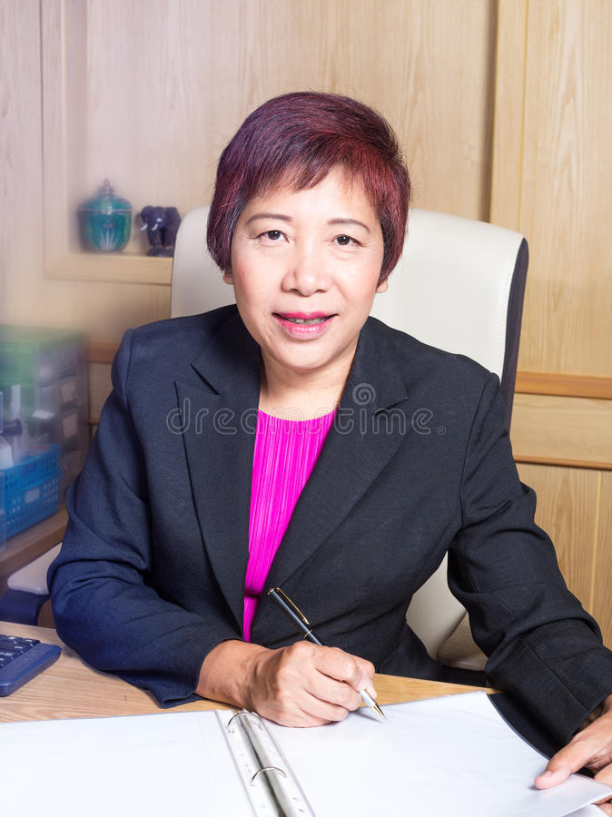 在书桌标志典雅文件的看起来的女商人亚裔经理资深年龄选址 库存照片