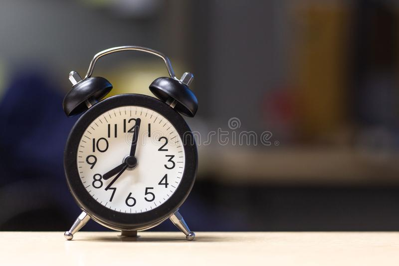 在书桌桌上的黑闹钟 库存照片
