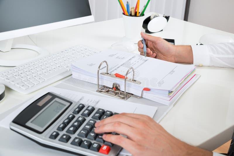 在书桌的买卖人计算的预算 库存图片
