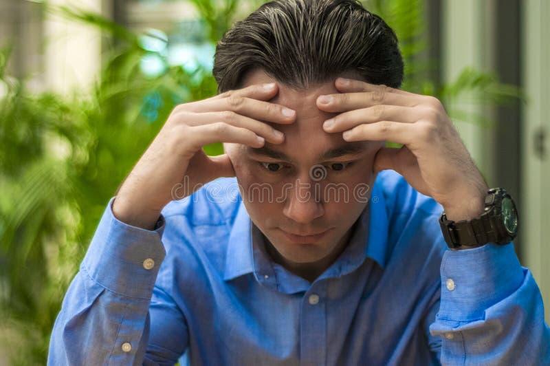 在书桌的哀伤,疲乏或者沮丧的商人 有问题和重音的商人在办公室 免版税库存图片