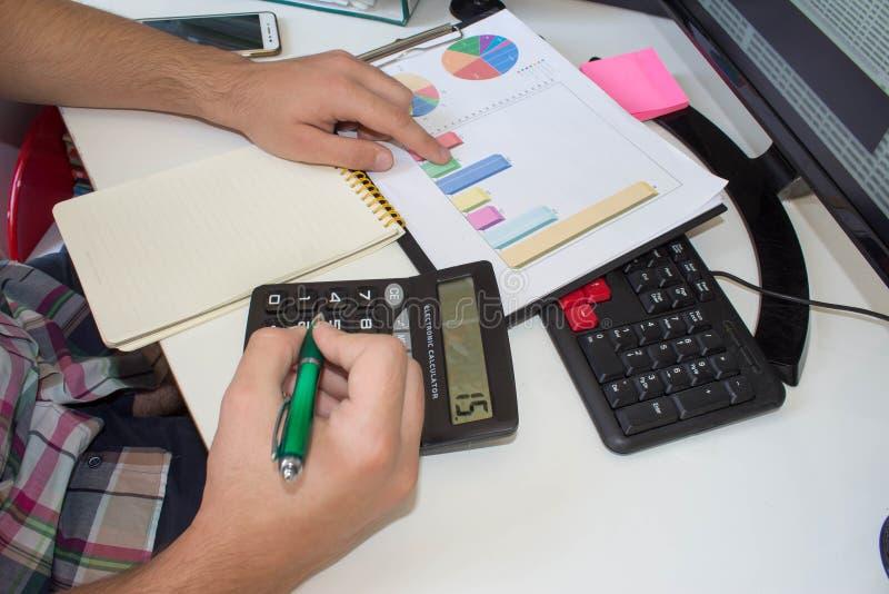 在书桌的商人使用一计算机,计算器和研究报告,手紧密  免版税库存图片