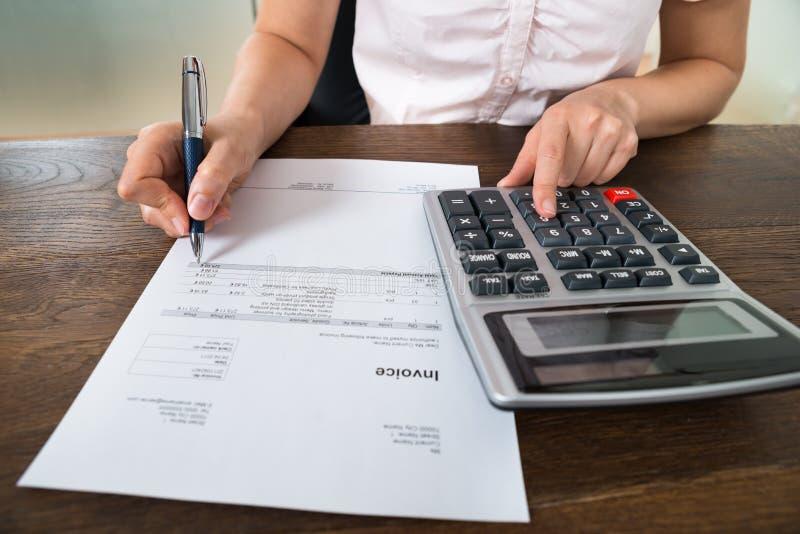 在书桌的女实业家计算的税 免版税库存图片