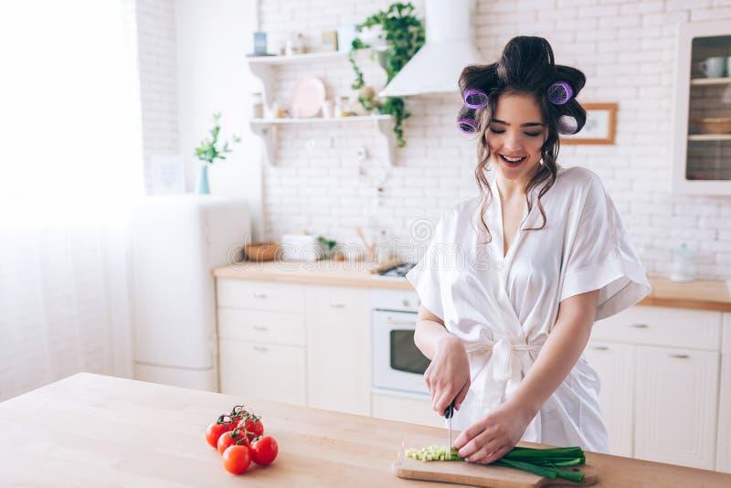 在书桌的年轻女性管家立场在厨房和裁减大葱 仔细的工作 在左边的被切的红辣椒 ?? 库存照片