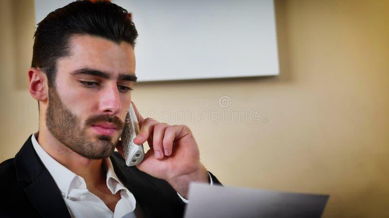 在书桌的微笑的英俊的年轻商人在电话 免版税库存图片