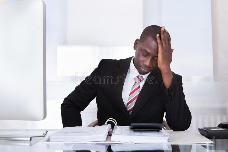 在书桌的沮丧的商人 库存图片