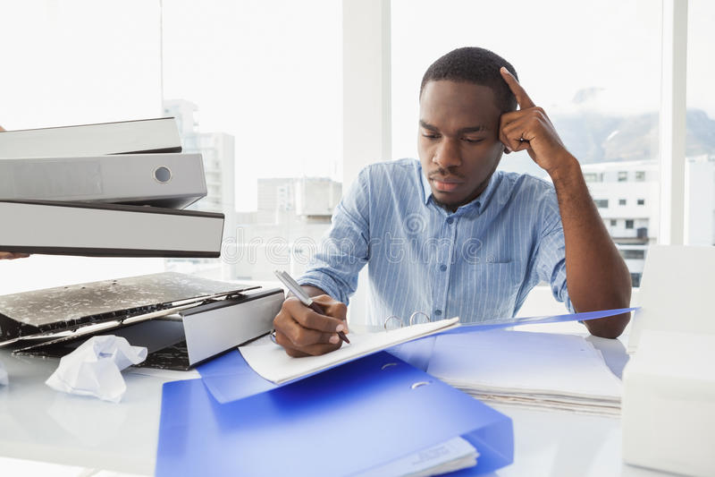 在书桌的疲乏的商人文字笔记 免版税库存图片