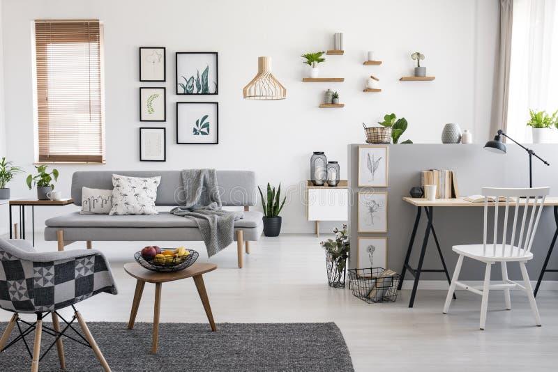 在书桌的白色椅子在与画廊的宽敞公寓内部在窗口附近的灰色沙发上 实际照片 免版税库存照片