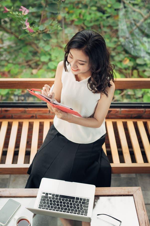 在书桌的美好的亚洲女孩文字笔记在家 库存照片