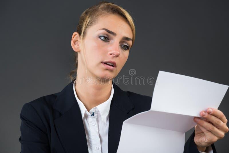 在书桌的震惊年轻女实业家读书信件 库存照片
