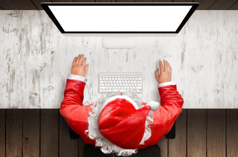 在书桌计算机上的圣诞老人工作有大模型的被隔绝的显示的 库存图片