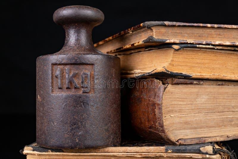 在书的老公斤重量 旧书和称量器 免版税图库摄影