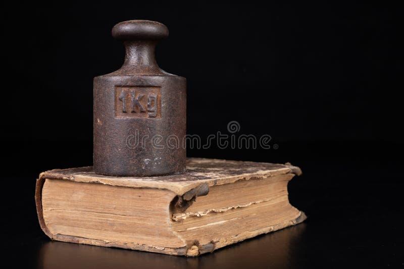 在书的老公斤重量 旧书和称量器 免版税库存图片