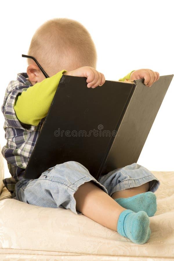 在书读书后的年轻男孩头 库存照片