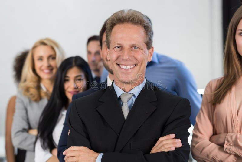 在买卖人小组背景的成功的商人上司,与商人队确信的举行的成熟领导人 图库摄影